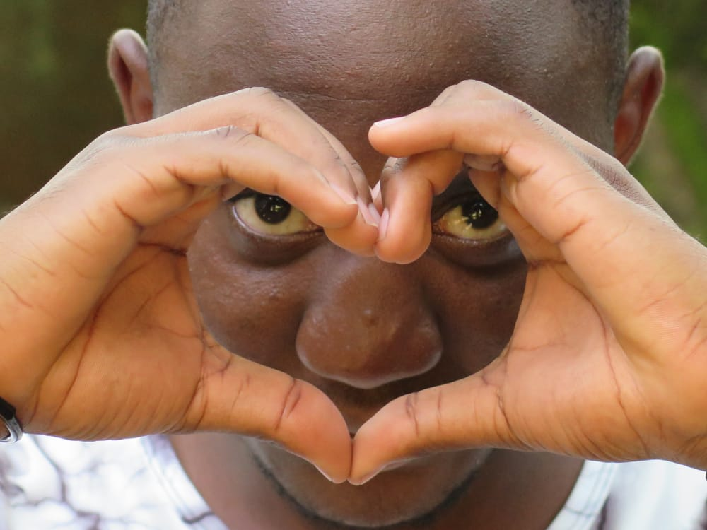 person with hands infront of face in the shape of a heart
